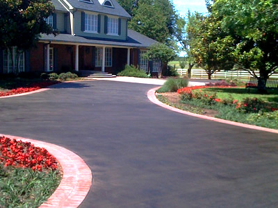 without the high impact red brick borders on this driveway its tediously stained centerpiece may be mistaken for regular ol pavement - Concrete Driveway Design Ideas